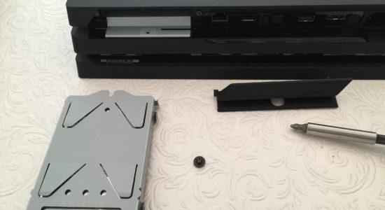 Skyddsluckan, skruven och vaggan med hårddisken i